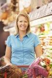 推挤台车的妇女由产物柜台在超级市场 免版税库存照片
