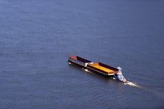 推挤在宽广的河的小拖轮两艘空的驳船 免版税库存图片