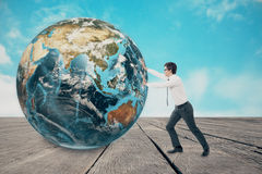 推挤在木地板上的商人地球 免版税库存图片