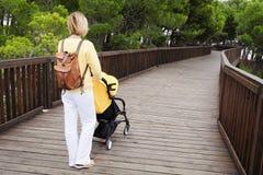 推挤在木桥的母亲一辆婴儿推车 免版税图库摄影