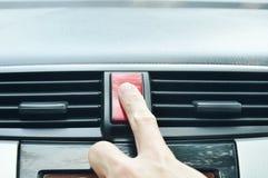 推挤在被打开的应急灯的红色按钮的手指在汽车 免版税库存照片