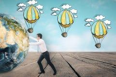 推挤地球的商人在天空的气球剪影附近 免版税库存图片