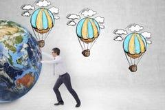 推挤地球的商人在气球剪影附近 免版税图库摄影