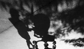 推挤婴孩台车的妇女的阴影 免版税图库摄影