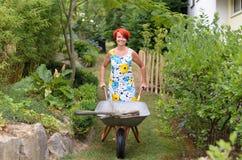 推挤有工具的愉快的妇女一辆独轮车 库存照片