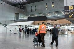 推挤机场的职员推挤轮椅的人在机场 免版税库存图片