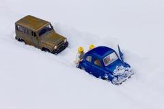 推挤汽车的两个人困住在雪 库存图片