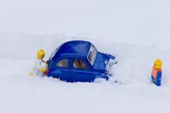 推挤汽车的人困住在雪 玩具模型 免版税图库摄影