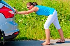 推挤汽车的妇女在汽油外面 免版税图库摄影