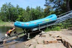 推挤河船在滑轮上的年轻人在与客人的游览, Ausable峡谷,纽约以后, 2018年 库存照片