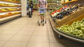 推挤沿杂货走道的年轻人推车在超级市场 走与购物台车的人在商店 股票录像