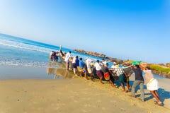 推挤渔船沙子海洋的科瓦兰村民 免版税库存照片