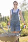 推挤独轮车的愉快的女性花匠画象在庭院 免版税图库摄影