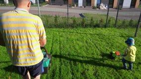 推挤玩具割草机的儿子,当爸爸割与他的时 r 股票录像