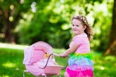 推挤玩具婴儿推车wth玩偶的小女孩 免版税库存照片