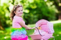 推挤玩具stoller wth玩偶的小女孩 免版税库存图片