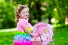 推挤玩具stoller wth玩偶的小女孩 图库摄影