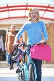 推挤自行车的母学生在教学日结束时 库存图片