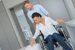 推挤轮椅的丈夫妻子 免版税库存图片