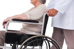 推挤轮椅的医生患者 免版税库存图片
