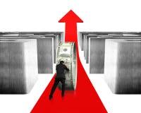 推挤金钱盘旋在红色箭头与迷宫 免版税库存照片
