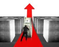 推挤金钱盘旋在红色箭头通过迷宫 免版税图库摄影