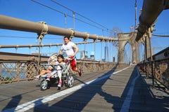 推挤婴儿推车的慢跑者在纽约 免版税库存图片