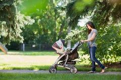 推挤婴儿推车的母亲在公园 图库摄影