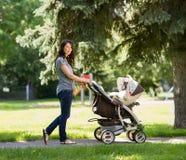 推挤婴儿推车的年轻母亲在公园 库存图片