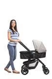 推挤婴儿车的快乐的母亲 免版税图库摄影