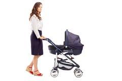 推挤婴儿车的母亲的全长画象 免版税库存图片