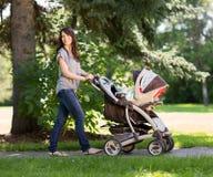 推挤婴儿车的美丽的母亲在公园 免版税库存照片