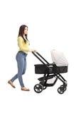 推挤婴儿车的年轻母亲 免版税图库摄影