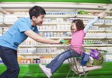 推挤购物车的父亲女儿在超级市场里面 免版税库存图片