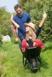 推挤他的独轮车的人女朋友 免版税图库摄影