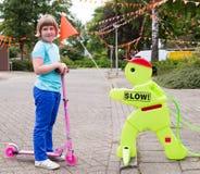 推挤滑行车的女孩有安全小雕象的 免版税库存照片