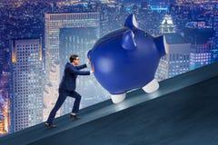 推挤piggybank上升在企业概念的人 免版税图库摄影