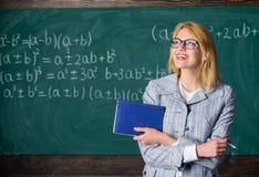 推荐打翻应用 巨大推荐书 妇女微笑的老师举行书摊前面黑板 免版税库存照片