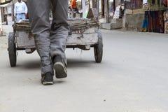 推进一辆老木头购物车的人 图库摄影