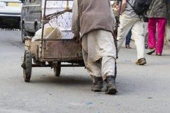 推进一辆老木头购物车的人 免版税库存照片