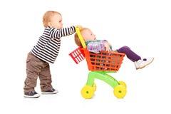 推进他的玩具购物车的小孩男孩双姐妹 免版税库存照片