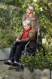推进垂直的轮椅妇女的母亲 图库摄影