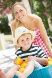 推进独轮车的母亲儿子 免版税库存照片