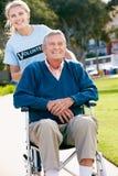 推进轮椅的少年志愿者老人 免版税库存照片