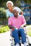 推进轮椅的高级妇女丈夫 免版税图库摄影