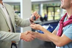 推销员与顾客握手,当在经销权,特写镜头中时给汽车钥匙 免版税库存照片