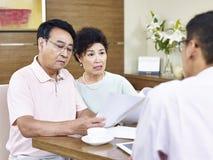 推销员冲击的资深亚洲夫妇 免版税库存照片
