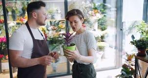 推销员咨询的顾客的慢动作然后给植物的花店的 股票录像