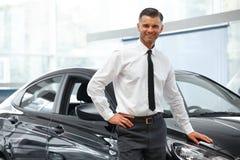推销员在全新的汽车附近站立 汽车陈列室 库存照片