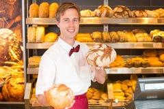 推销员在拿着面包的不同的类型面包店 库存图片